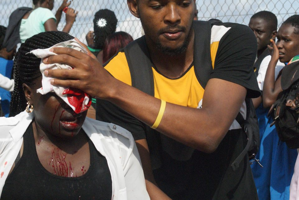 An injured official gets first aid treatment after being stoned by a Kyambogo student | PHOTO; KATUMBA BADRU