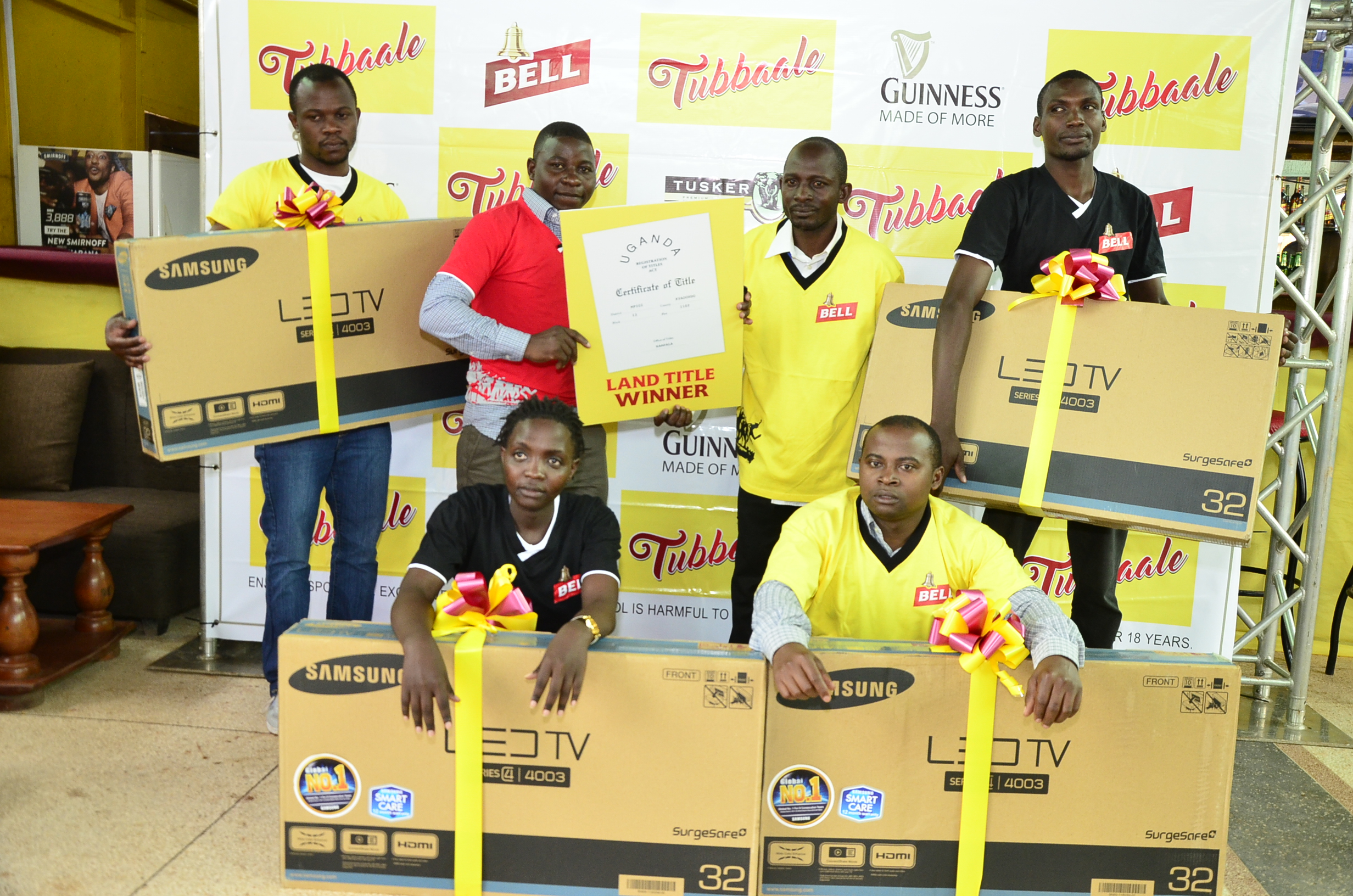 Winners of flat screen TVs and plots of land show off their prizes. A total of 38 televisions and 12 plots of land have so far been given away.
