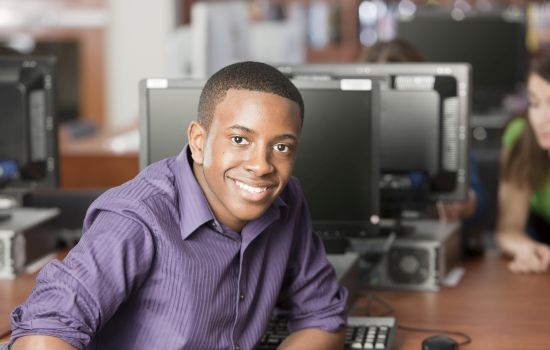 A head and shoulders image of a black teenage high school student using a computer in the school library. Shallow DOF.