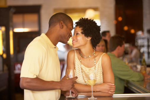 Young couple with drinks at bar in restaurant, smiling, side view