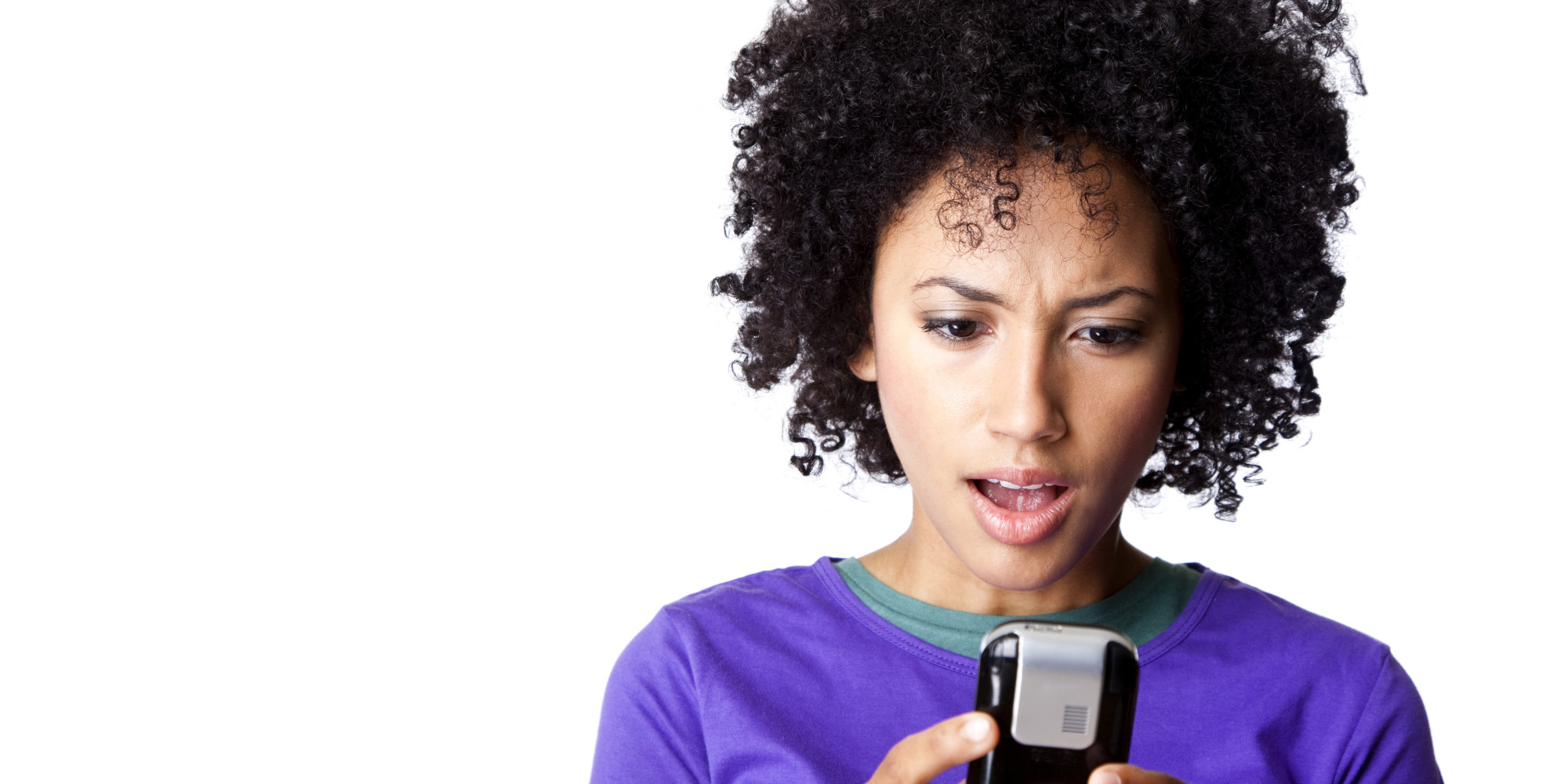 pretty young woman looking surprised at her text message