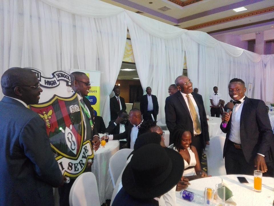 Hon:Rugunda Listens on as the MC hands over a portrait.