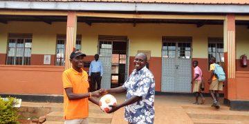 Kamuli branch operator handing over a ball to Kamuli township primary school gamesmaster