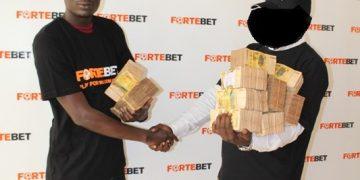 Fortebet's Davis Sebdagire handing over the money to the winner.